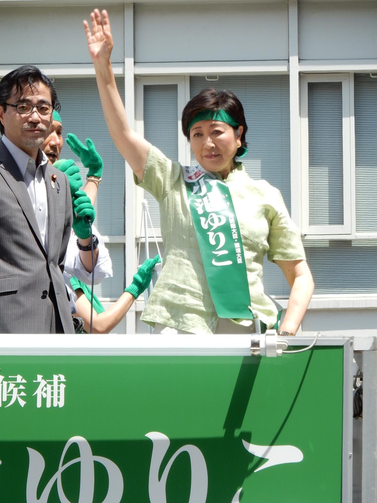 聴衆に手を上げ支持を訴える小池百合子氏