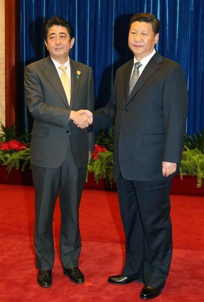 日中首脳会談を前に握手を交わす習近平国家主席(右)と安倍首相=10日、北京の人民大会堂
