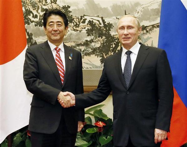 会談を前にロシアのプーチン大統領(右)と握手する安倍首相=9日、北京