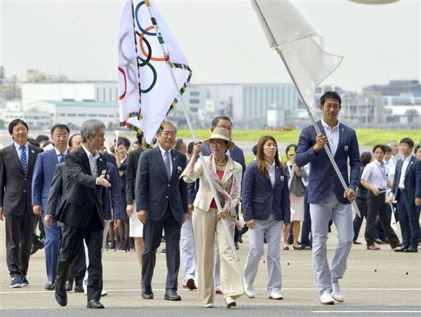 リオデジャネイロ五輪で引き継がれた五輪旗を手に羽田空港に到着した東京都の小池百合子知事(中央)=24日午前